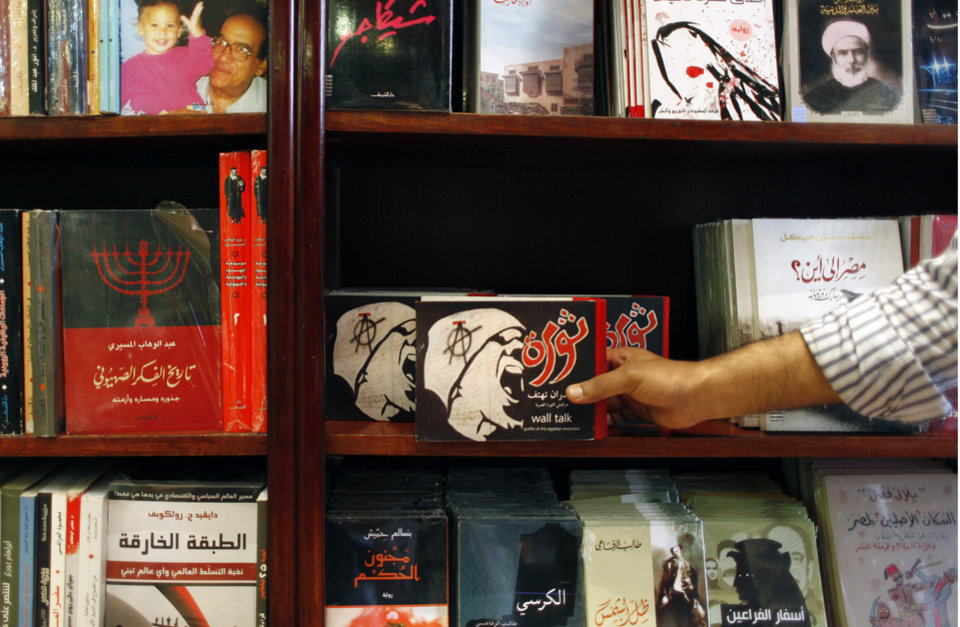 Photo -   In this Thursday, Oct. 4, 2012 photo, an Egyptian man picks out a copy of the 680 page pictorial book