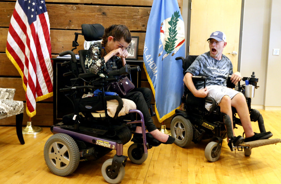 Photo -  Lori Taylor and Richard Anderson sit in the lobby of U.S. Sen. James Lankford's office as people with disabilities protest on Wednesday in Oklahoma City. [Photo by Steve Sisney, The Oklahoman]
