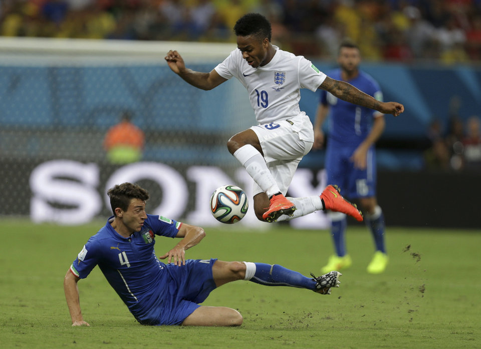 Photo - England's Raheem Sterling, top, is challenged by Italy's Matteo Darmian during the group D World Cup soccer match between England and Italy at the Arena da Amazonia in Manaus, Brazil, Saturday, June 14, 2014. (AP Photo/Martin Mejia)