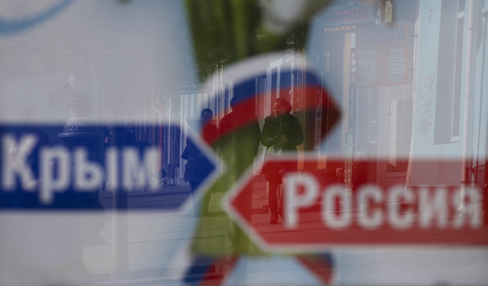 Photo - A couple's image reflected on an advertising board reading 'Russia, Crimea',  on a street in Simferopol, Ukraine, on Monday, March 17, 2014. Ukraine's Crimean peninsula declared itself independent Monday after its residents voted overwhelmingly to secede and join Russia, while the United States and the European Union slapped sanctions against some of those who promoted the divisive referendum. (AP Photo/Ivan Sekretarev)