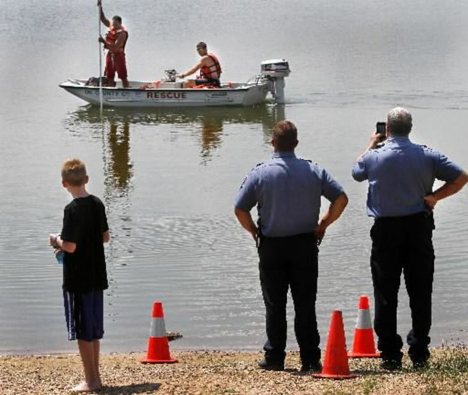 Photo - Del City firefighters look for a submerged van about about 75 feet from the bank at Eagle Lake on E. Reno, near Bryant, Thursday afternoon, July 12, 2012. Tommy Albertson rescued his two-year old grandson, Deshawn Robison, minutes before the van sank below the surface. PHOTO BY JIM BECKEL, The Oklahoman