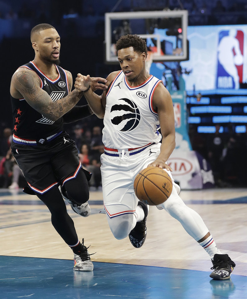 Photo - Team Giannis' Kyle Lowry, of the of the Toronto Raptors, moves past Team LeBron's Damian Lillard, of the Portland Trail Blazers during the first half of an NBA All-Star basketball game, Sunday, Feb. 17, 2019, in Charlotte, N.C. (AP Photo/Chuck Burton)