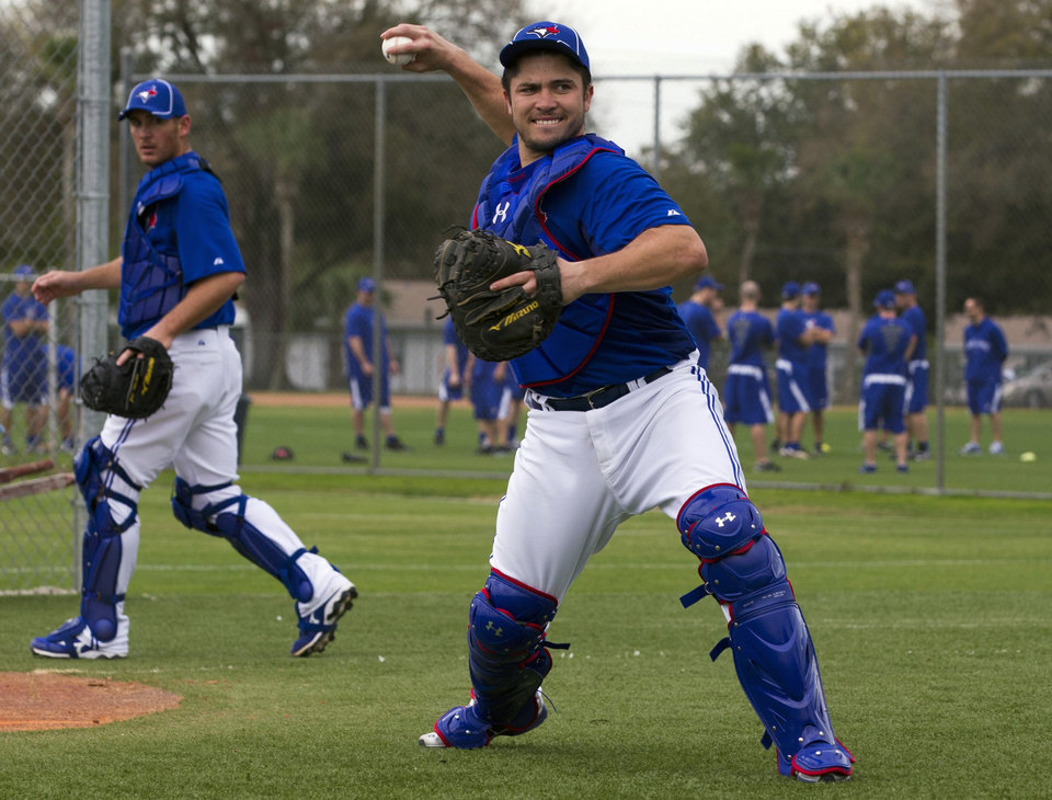 FILE - This Feb. 22, 2012 file photo shows Toronto Blue Jays catcher Travis d\'Arnaud, right, making a throw to first base as catcher Jeff Mathis, left, watches during the first official workout at spring training baseball in Dunedin, Fla. A person familiar with the deal tells The Associated Press that R.A. Dickey and the Blue Jays have agreed on a new contract, clearing the way for the New York Mets to trade the Cy Young winner to Toronto. The person spoke on condition of anonymity Monday, Dec. 17, 2012, because the trade was not yet complete. The Mets would get prized catching prospect Travis d\'Arnaud as the centerpiece of the multiplayer swap. (AP Photo/The Canadian Press, Frank Gunn)