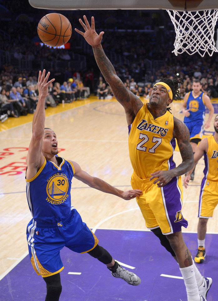 Photo - Golden State Warriors guard Stephen Curry, left, puts up a shot as Los Angeles Lakers forward Jordan Hill defends during the first half of an NBA basketball game, Friday, April 11, 2014, in Los Angeles. (AP Photo/Mark J. Terrill)