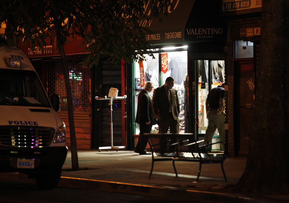 In this early Saturday, July 7, 2012 photo, authorities investigate the crime scene where clothing store owner Mohamed Gebeli was killed inside Valentino Fashion in the Bay Ridge neighborhood in the Brooklyn borough of New York. The same gun that killed Gebeli was also used in the murders of two other shopkeepers, according to police, with the latest victim being fatally shot Friday, Nov. 16, 2012, in Brooklyn\'s Flatbush neighborhood. (AP Photo/David Boe)