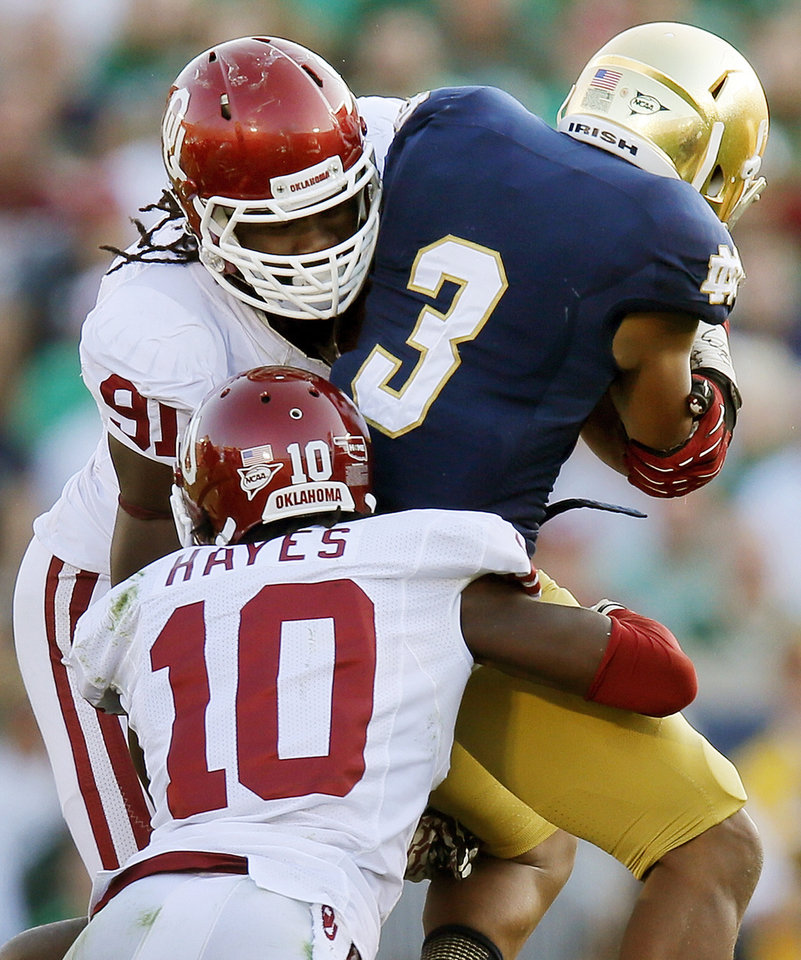 Photo - Oklahoma's Charles Tapper (91) and Quentin Hayes (10) stop Notre Dame's Amir Carlisle (3) in the third quarter during a college football game between the University of Oklahoma Sooners and the Notre Dame Fighting Irish at Notre Dame Stadium in South Bend, Ind., Saturday, Sept. 28, 2013. OU won, 35-21. Photo by Nate Billings, The Oklahoman