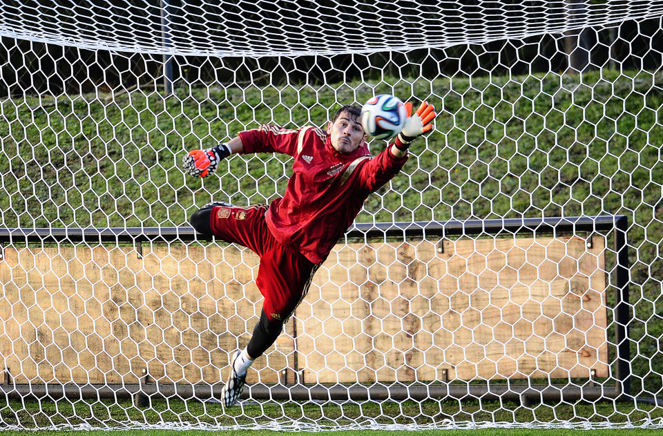 Photo - Spanish goalkeeper Iker Casillas, saves a ball during a training session of the Spanish national team at the Atletico Paranaense training center in Curitiba, Brazil, Monday, June 9, 2014. Spain will play in group B of the Brazil 2014 World Cup. (AP Photo/Manu Fernandez)