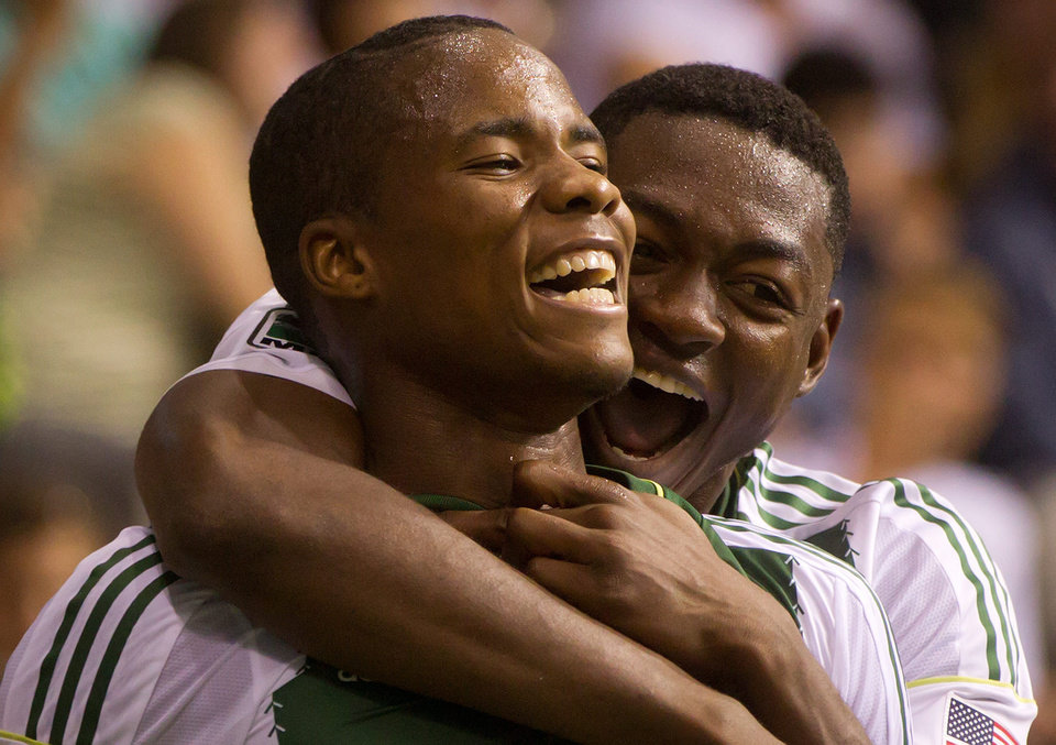 Photo - Portland Timbers' Alvas Powell, left, of Jamaica, and Fanendo Adi, of Nigeria, celebrate Powell's goal against the Vancouver Whitecaps during the second half of an MLS soccer game in Vancouver, British Columbia, on Saturday, Aug. 30, 2014. (AP Photo/The Canadian Press, Darryl Dyck)
