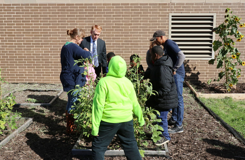 Photo - Sen. James Lankford assists in cutting okra in the garden class while he takes a tour of Thelma Parks Elementary School in Oklahoma City looking at the RESTORE OKC program there Tuesday, October 8, 2019. [Doug Hoke/The Oklahoman]