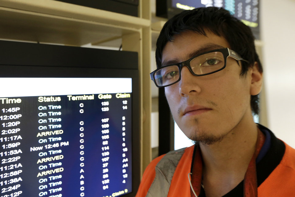 Photo - In this photo from Thursday, July 10, 2014, Irwin Carbajal, 23, a aircraft cabin cleaner, poses for a photograph at Newark Liberty International Airport in Newark, N.J. Carbajal, who makes $8.25 an hour, is hoping to benefit from a pay increase which the Service Employees International Union is pushing for. (AP Photo/Julio Cortez)