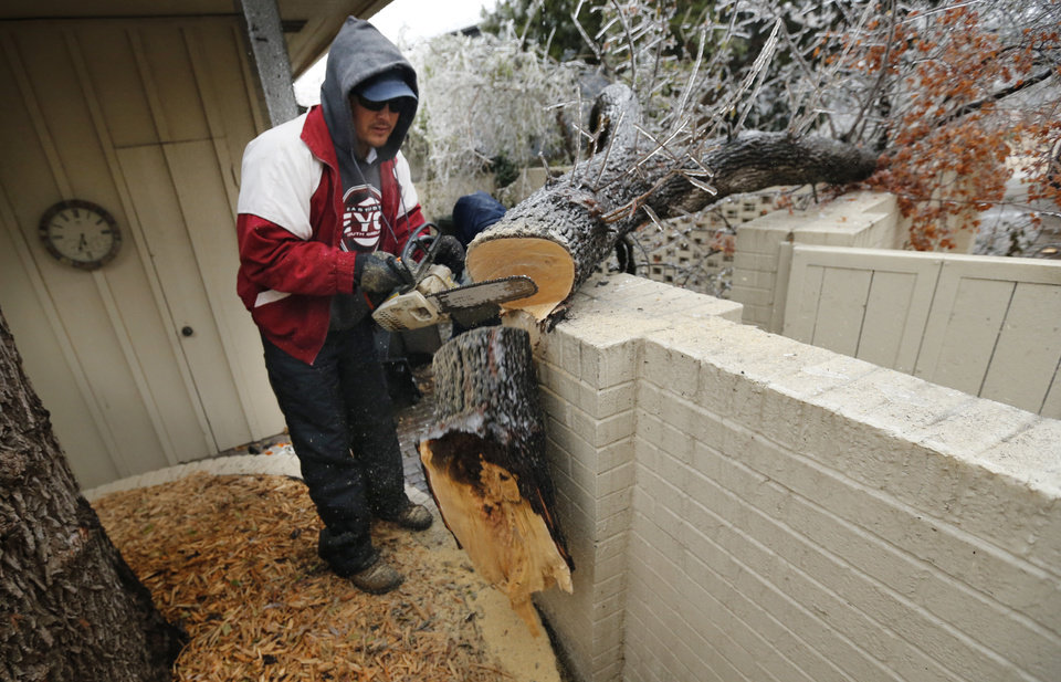 Photo - Carlos Ramires removes a limb from the wall at Murray Tabb's home after a winter storm coated trees with a thick layer of ice on Saturday, Dec. 21, 2013 in Norman, Okla.  Photo by Steve Sisney, The Oklahoman