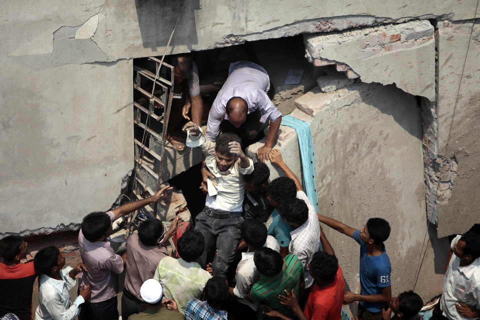 FILE - In this April 24, 2013 file photo, a man who was trapped in an eight-story building housing several garment factories is rescued after the structure collapsed in Savar, near Dhaka, Bangladesh. The owner of the building sits at the nexus of party politics and the powerful $20 billion garment industry that drives the economy of this deeply impoverished nation. Experts say this intersection of politics and business, combined with a minimum wage of $9.50 a week that has made Bangladesh the go-to nation for many of the world's largest clothing brands, has created a predictable danger for factory workers. Government officials, labor activists, manufacturers and retailers all called for improved safety standards after a November fire in the same suburb, when locked emergency exits trapped hundreds of garment workers inside amid spreading flames and 112 people died. But almost nothing has changed. (AP Photo/ A.M. Ahad, File)
