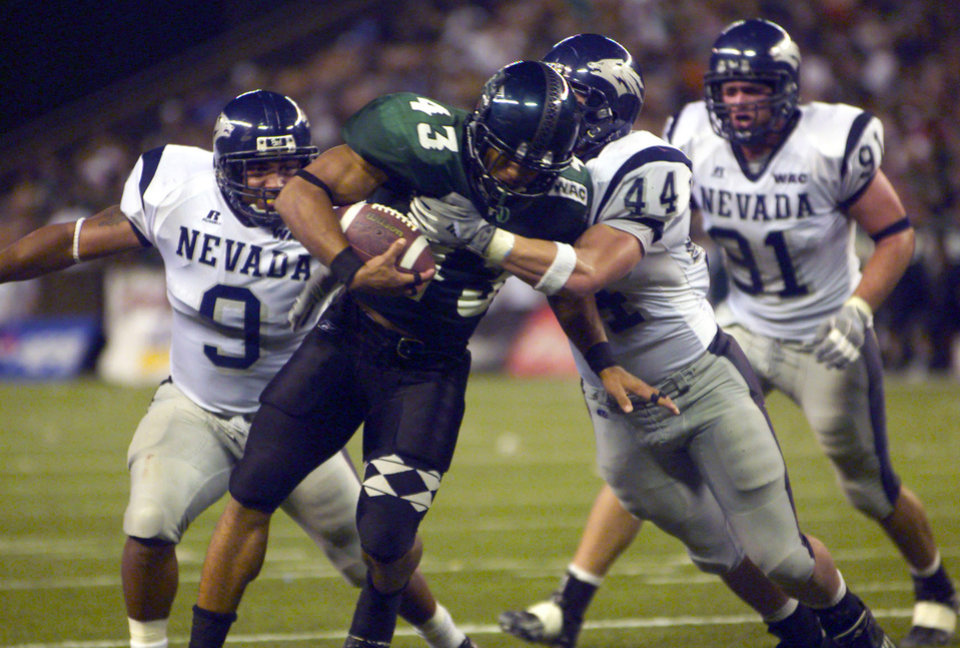 Photo - FILE - In this Oct. 9, 2004, file photo, Hawaii's Bryan Maneafaiga (43) scores a touchdown against Nevada in Honolulu. With uneven testing for steroids and inconsistent punishment, college football players are packing on significant weight _ in some cases, 30 pounds or more in a single year _ without drawing much attention from their schools or the NCAA in a sport that earns tens of billions of dollars for teams. But looking solely at the most significant weight gainers also ignores players like Maneafaiga. In the summer of 2004, Maneafaiga was an undersized 180-pound running back trying to make the University of Hawaii football team. Twice, once in pre-season and once in the fall, he failed school drug tests, showing up positive for marijuana use. What surprised him was that the same tests turned up negative for steroids. He'd started injecting stanozolol, a steroid, in the summer to help bulk up to a roster weight of 200 pounds. (AP Photo/ Honolulu Star-Advertiser, George F. Lee)