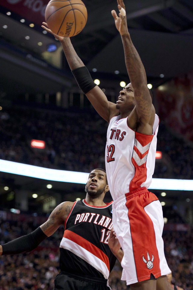 Photo - Toronto Raptors' Ed Davis (32) grabs a loose ball in front of Portland Trail Blazers' LaMarcus Aldridge during the first quarter of an NBA basketball game in Toronto, Wednesday, Jan. 2, 2013. (AP Photo/The Canadian Press, Frank Gunn)