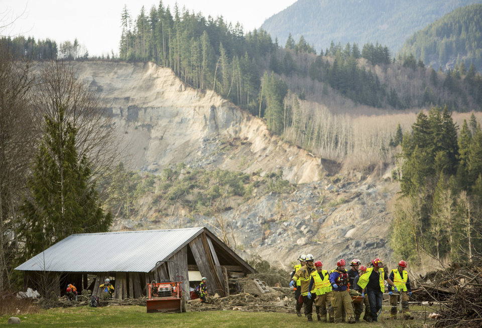 Photo - Rescue workers remove one of a number of bodies from the wreckage of homes destroyed by a mudslide near Oso, Wash., Monday, March 24, 2014. The search for survivors of Saturday's deadly mudslide grew Monday to include scores of people who were still unaccounted for as the death toll from the wall of trees, rocks and debris that swept through the rural community rose to at least 14. (AP Photo/seattlepi.com, Joshua Trujillo)