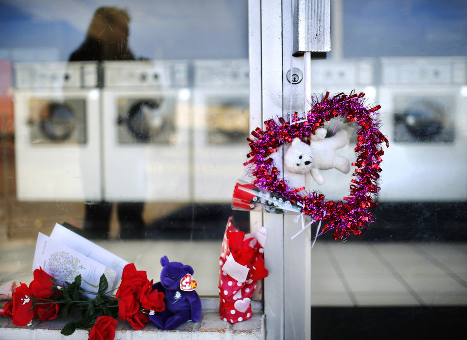 "Photo - Kandi Mealy, 52, of Del City, put the colorful heart-shaped wreath and the while teddy bear on the front door. Mealy said she was a regular customer at the business and described victim Nekia Jackson as ""personable,"" and ""helpful.""  A day after two people were shot and killed at a Del City coin operated laundry business, customers and friends continue to bring items to a makeshift memorial to the woman and man who were killed yesterday inside the Laundry Station, 4000 SE 15, in Del City, shortly before it opened for business Monday.  The woman is identified as Nekia Jackson, an employee at the business. Photo by Jim Beckel, The Oklahoman"