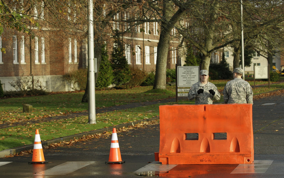 Photo -   Two soldiers stand guard at a road closed for construction outside the building housing a military courtroom on Joint Base Lewis McChord in Washington state, where a preliminary hearing was expected to conclude Tuesday Nov. 13, 2012, for U.S. Army Staff Sgt. Robert Bales. Bales is accused of 16 counts of premeditated murder and six counts of attempted murder for a pre-dawn attack on two villages in Kandahar Province in Afghanistan last March. (AP Photo/Ted S. Warren)