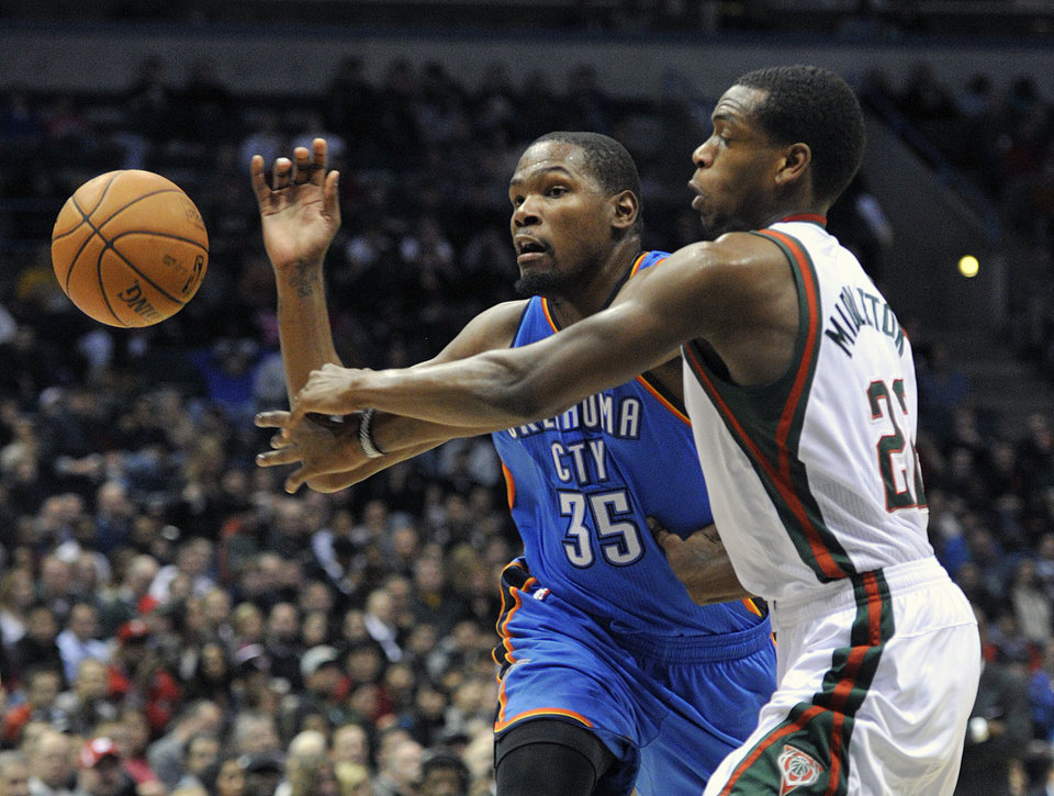 Photo - Oklahoma City Thunder's Kevin Durant (35) and Milwaukee Bucks' Khris Middleton scramble for a loose ball during the first half of an NBA basketball game Saturday, Nov. 16, 2013, in Milwaukee. (AP Photo/Jim Prisching)