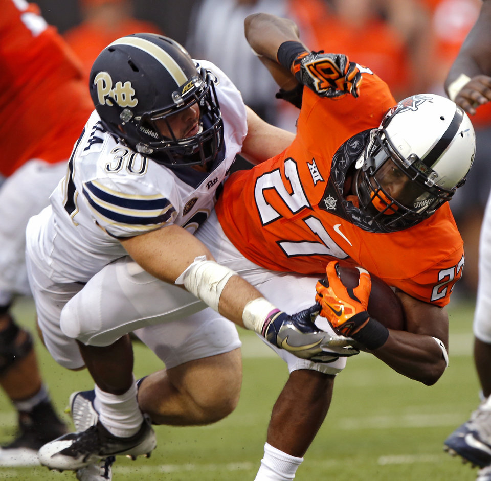 Photo - Pittsburgh's Mike Caprara (30) stops Oklahoma State's Justice Hill (27) for a loss during a college football game between the Oklahoma State Cowboys (OSU) and the Pitt Panthers at Boone Pickens Stadium in Stillwater, Okla., Saturday, Sept. 17, 2016. Photo by Chris Landsberger, The Oklahoman