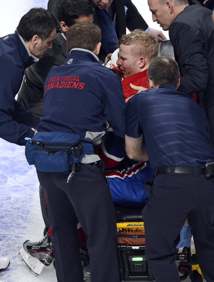 Photo - Montreal Canadiens center Lars Eller is placed onto a stretcher after being checked by Ottawa Senators defenseman Eric Gryba during the second period of Game 1 of an NHL hockey Stanley Cup playoffs first-round series in Montreal on Thursday, May 2, 2013. (AP Photo/The Canadian Press, Ryan Remiorz)