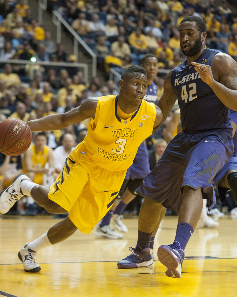 Photo - West Virginia's Juwan Staten, left, drives past Kansas State's Thomas Gipson during the second half of an NCAA college basketball game Saturday, Feb. 1, 2014, in Morgantown, W.Va. West Virginia won 81-71. (AP Photo/Andrew Ferguson)