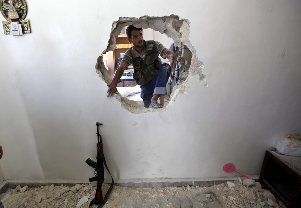 Photo -   A Syrian fighter jumps through a hole punched in a wall during a search for survivors buried in the rubble of a building hit by an airstrike in Aleppo, Syria, Friday, Aug. 17, 2012. Rebel footholds in Aleppo have been the target of weeks of Syrian shelling and air attacks as part of wider offensives by President Bashar Assad's regime. Rebels have been driven from some areas, but the report of clashes near the airport suggests the battles could be shifting to new fronts. (AP Photo/Khalil Hamra)