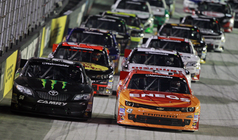 Photo - Kyle Busch (54) races with JJ Yeley (42) during the NASCAR Nationwide series auto race at Bristol Motor Speedway on Friday, Aug. 22, 2014, in Bristol, Tenn. (AP Photo/Wade Payne)