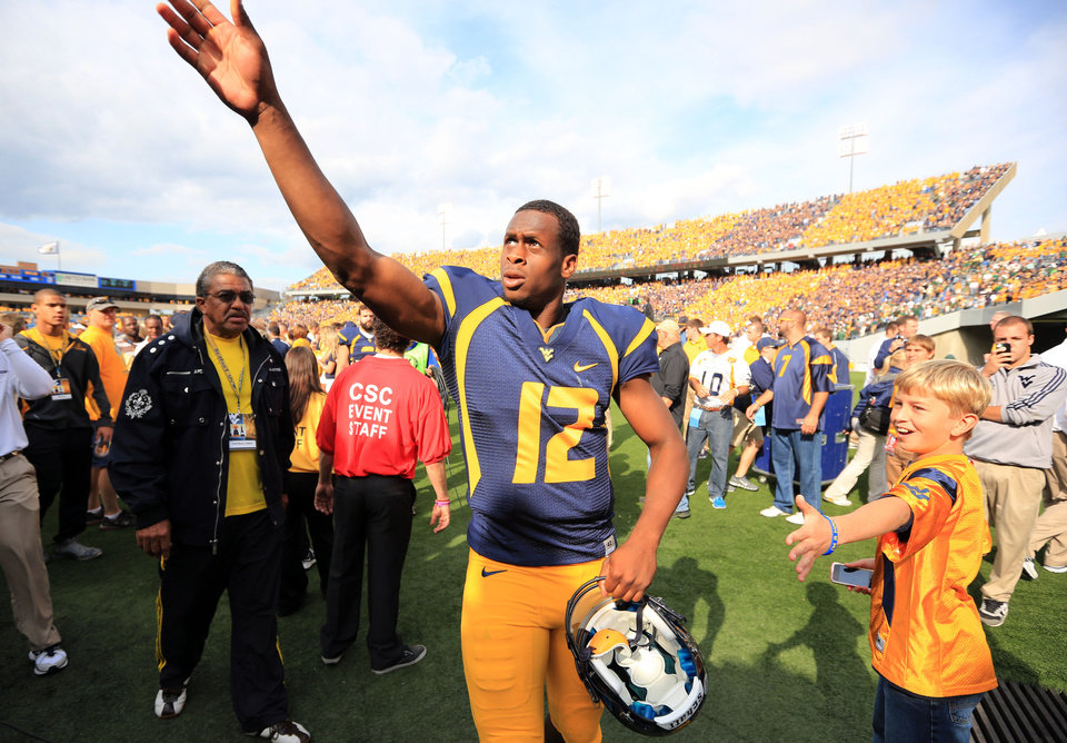 Photo - West Virginia quarterback Geno Smith gestures to fans after their NCAA college football game against Baylor in Morgantown, W.Va., Saturday, Sept. 29, 2012. Smith threw for 656 yards and tied a Big 12 record with eight touchdown passes to lead No. 9 West Virginia to a 70-63 win over No. 25 Baylor . (AP Photo/Christopher Jackson)   ORG XMIT: WVCJ106