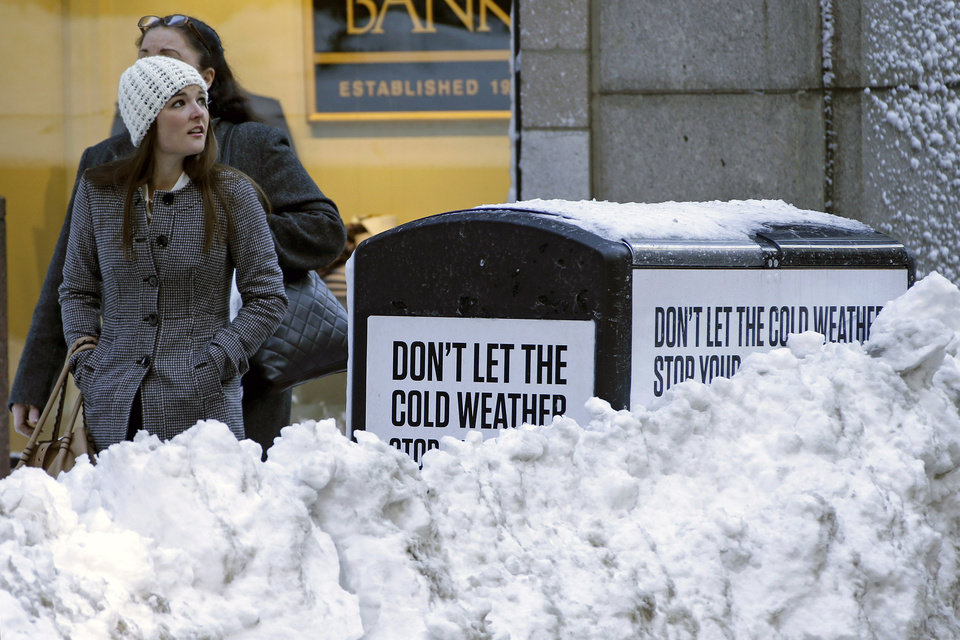 Photo - A woman walks through downtown Boston on a sunny Sunday afternoon, Feb. 10, 2013. The city continues to dig out from the two-feet off snow that fell on Friday and Saturday. (AP Photo/Gene J. Puskar)