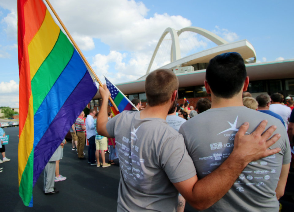 Photo - Corey Kehn, left, holding flag, and Benjamin Ault during the marriage equality victory rally at Freedom Oklahoma parking lot, Friday, June 26, 2015. Photo by Doug Hoke, The Oklahoman | Imported: Fri. Jun 26, 2015 at 8:30pm