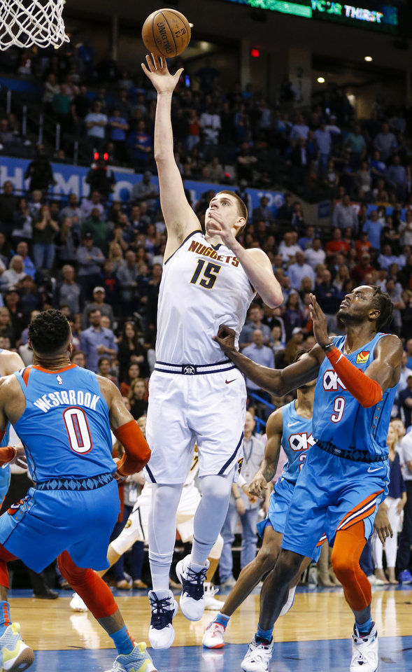 Photo - Denver's Nikola Jokic (15) scores between Oklahoma City's Russell Westbrook (0) and Jerami Grant (9) in the fourth quarter during an NBA basketball game between the Denver Nuggets and the Oklahoma City Thunder at Chesapeake Energy Arena in Oklahoma City, Friday, March 29, 2019. Denver won 115-105. Photo by Nate Billings, The Oklahoman