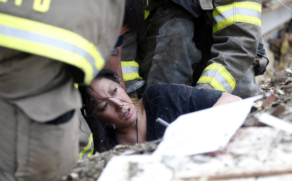 Photo - A woman is pulled out from under tornado debris at the Plaza Towers School in Moore, Okla., Monday, May 20, 2013. A tornado as much as a mile (1.6 kilometers) wide with winds up to 200 mph (320 kph) roared through the Oklahoma City suburbs Monday, flattening entire neighborhoods, setting buildings on fire and landing a direct blow on an elementary school. (AP Photo Sue Ogrocki)