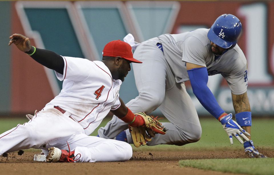 Photo - Los Angeles Dodgers' Matt Kemp slides safely into second base with a double as Cincinnati Reds second baseman Brandon Phillips (4) applies the late tag in the fourth inning of a baseball game, Monday, June 9, 2014, in Cincinnati. (AP Photo/Al Behrman)