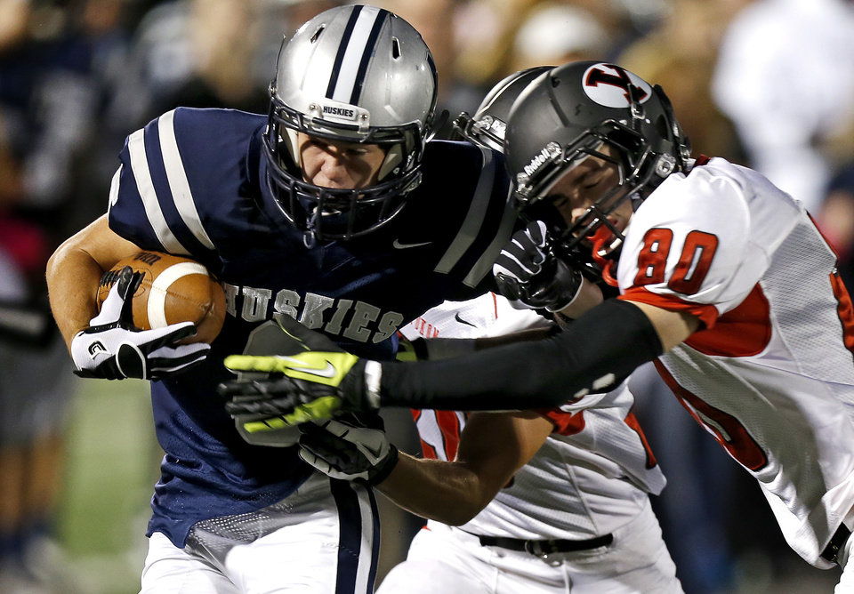 Photo - Edmond North's Robert Secrets is brought down by Yukon's Zayne Nave during a high school football game at Wantland Stadium in Edmond, Okla., Thursday, October 4, 2012. Photo by Bryan Terry, The Oklahoman
