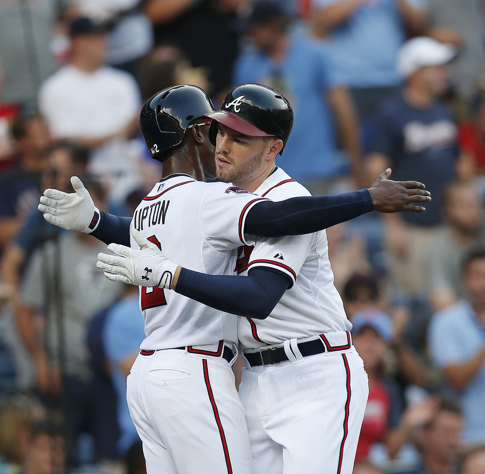 Photo - Atlanta Braves first baseman Freddie Freeman, right, hugs B.J. Upton  after hitting a three-run home run in the second inning of baseball game against the Miami Marlins  in Atlanta, Wednesday, July 23, 2014. (AP Photo)
