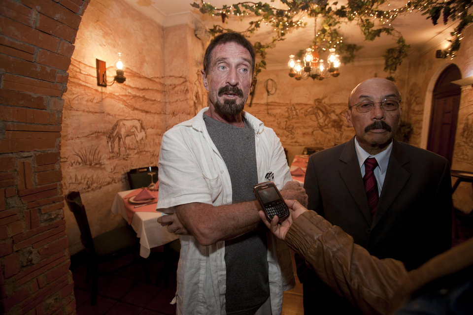 Photo - Software company founder John McAfee, left, accompanied by his lawyer Telesforo Guerra, right, answers questions during an interview at a local restaurant in Guatemala City, Tuesday, Dec. 4, 2012.  McAfee, 67, has been identified as a