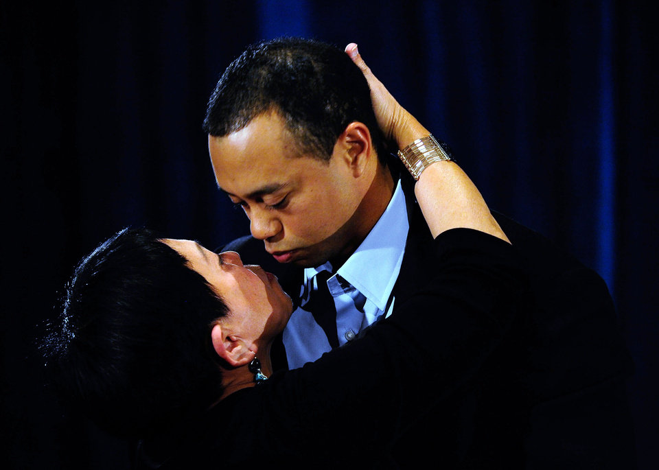 Photo - Tiger Woods kisses his mother Kultida Woods after making a statement at the Sawgrass Players Club, Friday, Feb. 19, 2010, in Ponte Vedra Beach, Fla. (AP Photo/Sam Greenwood, Pool) ORG XMIT: TWP117