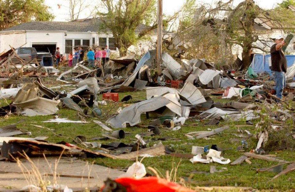 Photo -  Quapaw residents survey the damage in a residential neighborhood struck by a tornado on Sunday evening. GARY CROW, For the Tulsa World      -