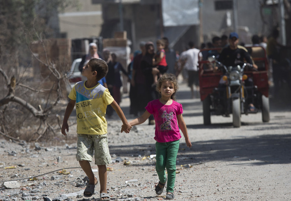 Photo - Palestinian children walk hand in hand as residents return to the heavily bombed Gaza City neighborhood of Shijaiyah, close to the Israeli border, Friday, Aug. 1, 2014. A three-day Gaza cease-fire that began Friday quickly unraveled, with Israel and Hamas accusing each other of violating the truce as several Palestinians were killed in a heavy exchange of fire in the southern town of Rafah. (AP Photo/Dusan Vranic)