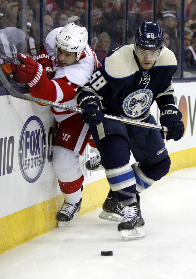 Photo - Detroit Red Wings' David Legwand, left, and Columbus Blue Jackets' David Savard work for the puck in the first period of an NHL hockey game in Columbus, Ohio, Tuesday, March 25, 2014. (AP Photo/Paul Vernon)