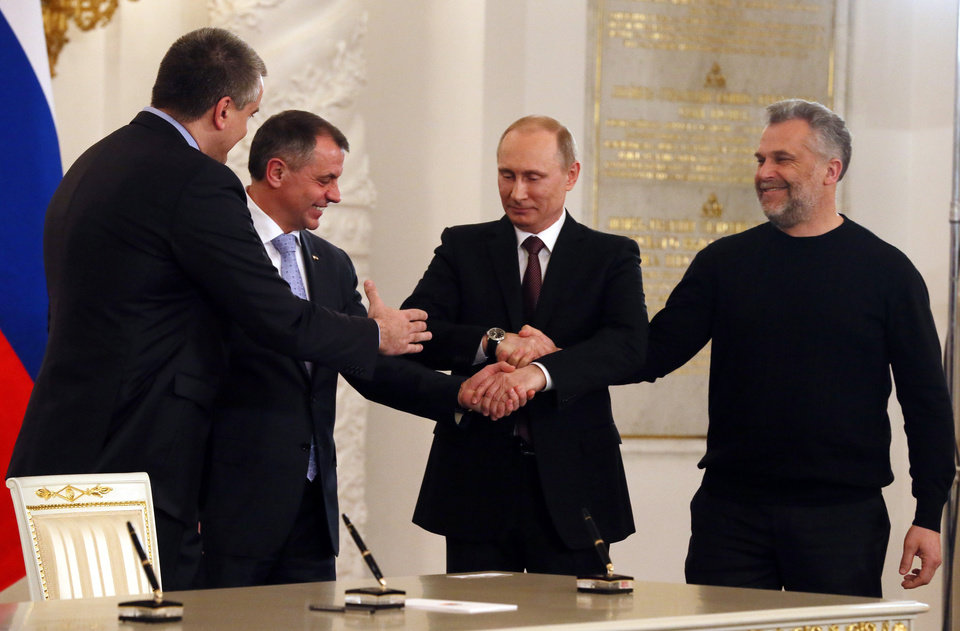 Photo - Russian President Vladimir Putin, second right, Speaker of Crimean legislature Vladimir Konstantinov, second left, Crimean Premier Sergei Aksyonov, left, and Sevastopol mayor Alexei Chalyi, right, shake hands after signing a treaty for Crimea to join Russia in the Kremlin in Moscow,  Tuesday, March 18, 2014. President Vladimir Putin on Tuesday signed a treaty to incorporate Crimea into Russia, describing the move as the restoration of historic injustice and a necessary response to what he called the Western encroachment on Russia's vital interests.   (AP Photo/Sergei Ilnitsky, Pool)