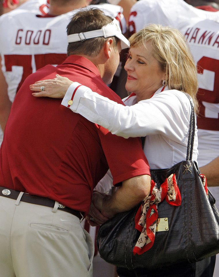 Photo - OU head coach Bob Stoops gets a hug from Gov. Mary Fallin after the Red River Rivalry college football game between the University of Oklahoma Sooners (OU) and the University of Texas Longhorns (UT) at the Cotton Bowl in Dallas, Friday, Oct. 7, 2011. OU won, 55-17. Photo by Nate Billings, The Oklahoman