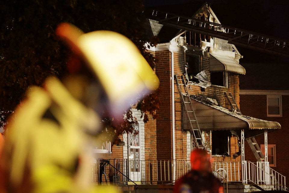 Officials stand in front of a fire-damaged house in Baltimore, where an early morning fire claimed the lives of an adult and four children Thursday, Oct. 11, 2012. (AP Photo/Patrick Semansky)