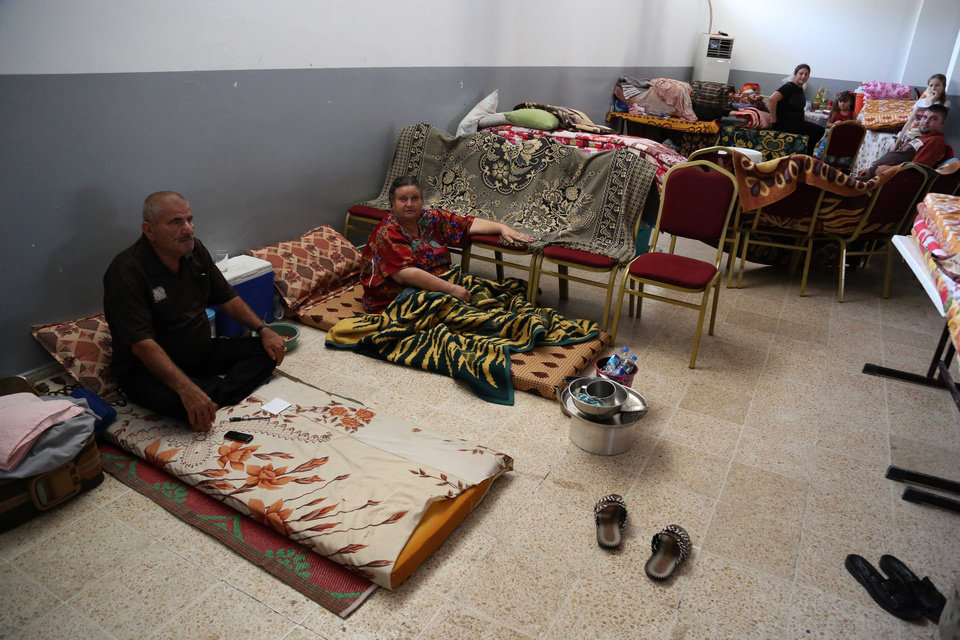 Photo - Displaced Iraqi Christians and Yazidis settle at diocese of Zakho, 300 miles (475 kilometers) northwest of Baghdad, Iraq, Saturday, Aug. 16, 2014. Islamic extremists shot 80 Yazidi men to death in Iraq, lining them up in small groups and opening fire with assault rifles before abducting their wives and children, officials and eyewitnesses reported Saturday. (AP Photo/ Khalid Mohammed)