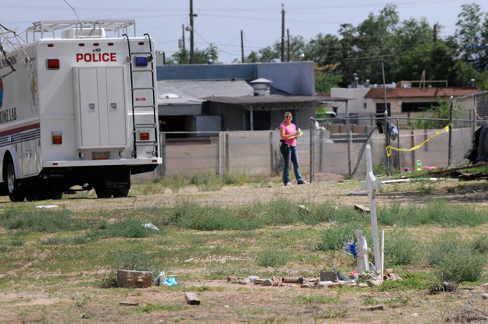 Photo - In a Saturday, July 19, 2014 photo, Albuquerque police work at the scene where two men were found dead in a open area just north of Central Avenue at 60th Street. Three teenagers are being held in Bernalillo County detention facilities a day after allegedly killing the two sleeping men in an open field in an attack so violent it left the victims unrecognizable, police spokesman Simon Drobik said. A third man said he was able to escape. (AP Photo/Albuquerque Journal, Jim Thompson) MANDATORY CREDIT