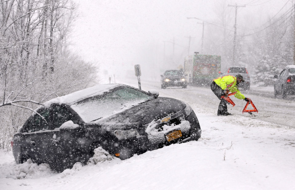 Photo - Tow truck operator Shawn Juhre sets up road safety reflectors before towing a car out of a ditch during a winter snow storm in Buffalo, N.Y., Friday, Feb. 8, 2013. Snow began falling across the Northeast on Friday, ushering in what was predicted to be a huge, possibly historic blizzard and sending residents scurrying to stock up on food and gas up their cars. The storm could dump 1 to 3 feet of snow from New York City to Boston and beyond. (AP Photo/David Duprey)