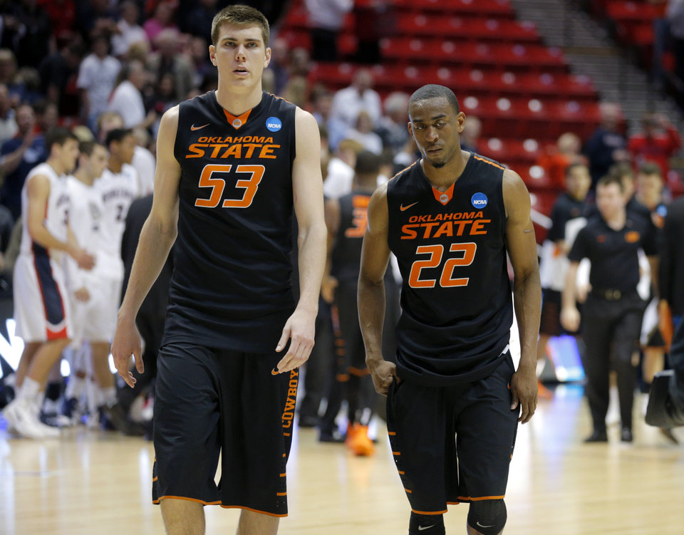 Photo - Oklahoma State's Mason Cox (53) and Markel Brown (22) walk off the court after losing a second round game of the NCAA men's college basketball tournament at Viejas Arena in San Diego, between Oklahoma State and Gonzaga Friday, March 21, 2014. Gonzaga won 85-77. Photo by Bryan Terry, The Oklahoman