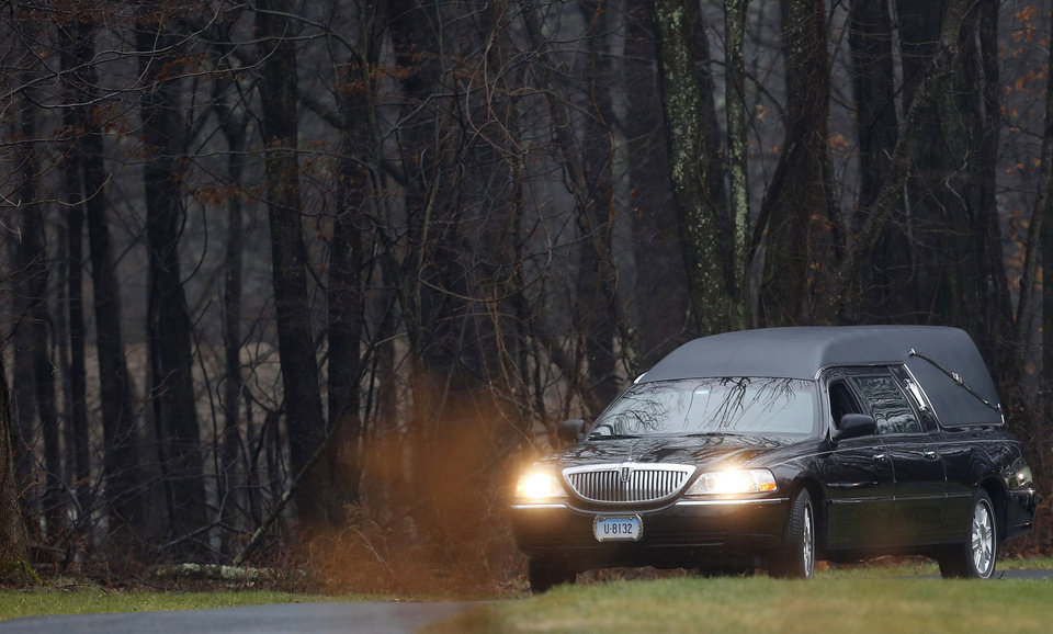 Photo - A hearse arrives at B'nai Israel Cemetery with the body of Noah Pozner, a six-year-old killed in an elementary school shooting, during funeral services, Monday, Dec. 17, 2012, in Monroe, Conn. Authorities say gunman Adam Lanza killed his mother at their home on Friday and then opened fire inside the Sandy Hook Elementary School in Newtown, killing 26 people, including 20 children, before taking his own life. (AP Photo/Julio Cortez) ORG XMIT: CTJC122