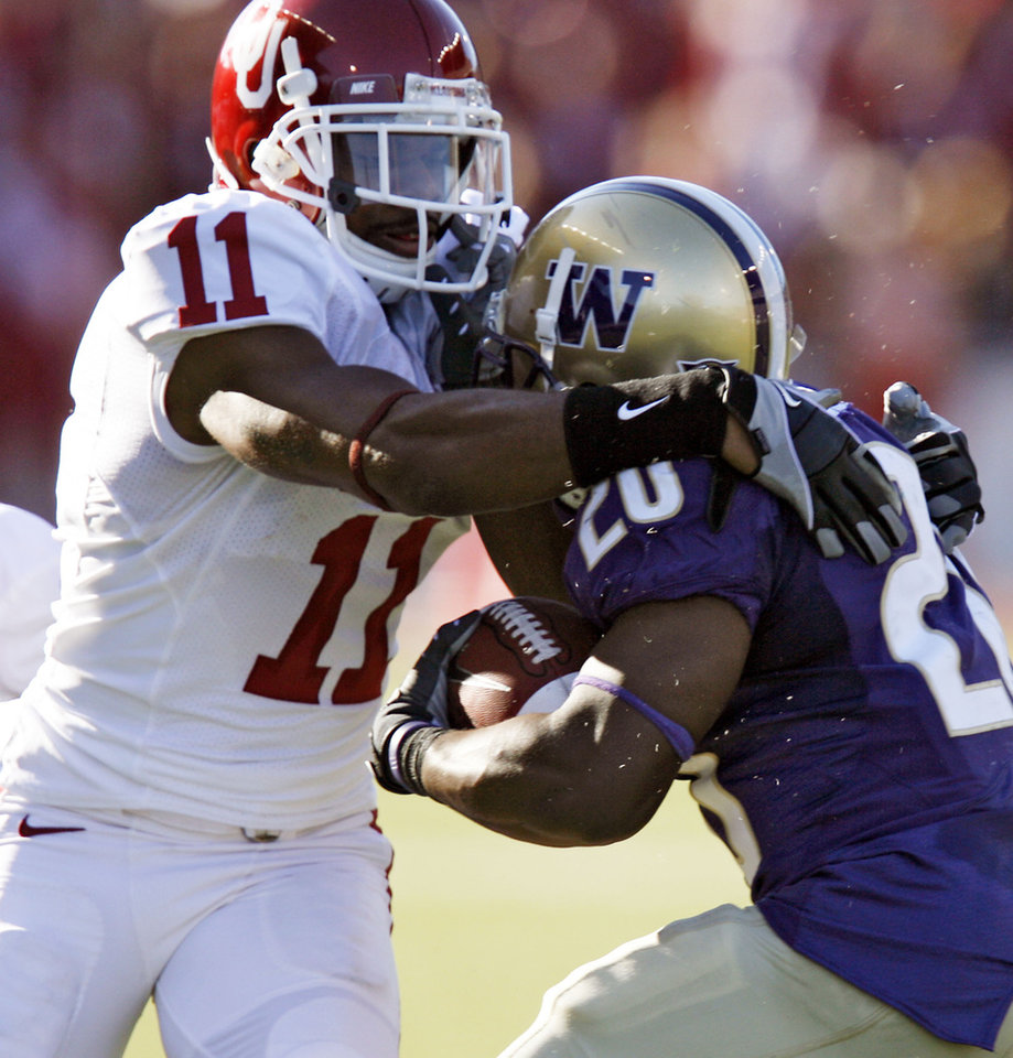 Photo - Oklahoma's Lendy Holmes (11) stops Washington's David Freeman (20) for a loss during the first half of the college football game between the University of Oklahoma Sooners (OU) and the University of Washington Huskies (UW) at Husky Stadium on Saturday, Sep. 13, 2008, in Seattle, Wash. 