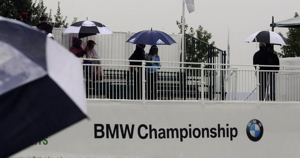 Photo - Fans huddle under umbrellas as they wait for play to resume during a rain delay in the final round of the BMW Championship golf tournament at Conway Farms Golf Club in Lake Forest, Ill., Sunday, Sept. 15, 2013. (AP Photo/Matt Marton)